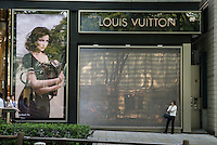 Woman waiting outside Louis Vuitton store in Omote-Sando dori, Tokyo, Japan with a poster representing actress/model Leatitia Casta.