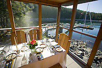 T'ai Li lodge on Cortes Island boasts intimate waterfront dining complete with a view of the sailboats.  Cortes Island, British Columbia, Canada