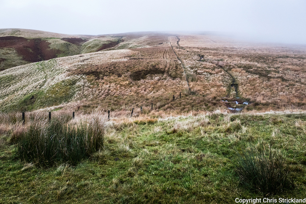 Looking north east along the Pennine Way and Anglo Scot Border towards Lamb Hill on a foggy November afternoon from Yearning Saddle, in the Cheviot Hills.