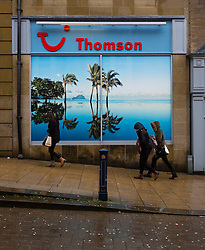 ©Paul Thompson Licensed to London News Pictures. 30/11/2015. Huddersfield West Yorkshire. Heavy rain in Huddersfield. People sheltering from the rain while walking past a poster in a Thomson Travel agents showing a sun drenched island with palm trees. Photo credit : Paul Thompson/LNP