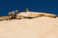 Man assisting woman climbing cliff low angle view