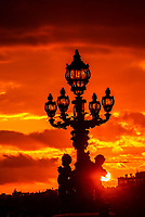 One of the Art Nouveau lamps (with cherubs) of the Pont Alexandre III (bridge) across the River Seine silhouetted at sunset. It is the most ornate bridge in Paris, France.