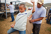 14 JULY 2012 - OAK SPRINGS, AZ:  KIRBY SHERMAN helps his son, KIRMIYAH SHERMAN, 6, master the basics of bull riding at the Aspen Canyon Rodeo Club in Oak Springs. The bull riding class was offered by the Crooked Horn Cattle Co. in the community of Oak Springs on the Navajo Nation, about 15 miles south of Window Rock, AZ. Eleven cowboys signed up for bull riding classes and one signed up for bull fighting classes. The bull riding class started with lessons on a mechanical bucking machine before the cowboys rode bulls.   PHOTO BY JACK KURTZ