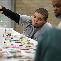 Jonathan Crump, 12 of Plantersville, washes out his paint brush as he helps paints decorative pieces that will be put on the community blessing box on Thursday night at the Lee County Library in Tueplo.