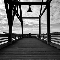 Lone person standing at end of pier looking into clouds and body of water.