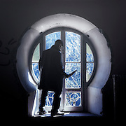a man with a knife in front of an old window in an abandoned building
