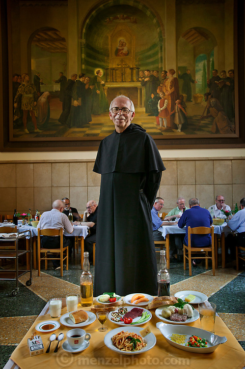 Riccardo Casagrande, a Roman Catholic friar and gastronome, in the San Marcello al Corso church dining hall in Rome, Italy, with his typical day's worth of food. (From the book What I Eat: Around the World in 80 Diets.)  The caloric value of his typical day's worth of food on a day in July was 4000 kcals. He is 63 years of age; 5 feet, 8.5 inches tall; and 140 pounds. For over 20 years he has overseen the kitchen, the rooftop garden, and the basement wine cellar for the friars and priests living in the church complex near Rome's Spanish Steps.   Between stints saying mass in the beautiful San Marcello al Corso in Rome, he is in charge of his fellow brothers' wine cellar, and oversees the cooks. Traditional Italian food is served family style in the brothers' large dining room. MODEL RELEASED.