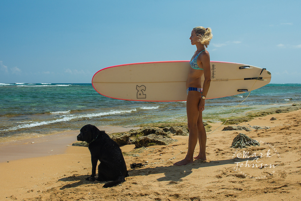 Woman surfer and her black labrador pet dog on the beach, Hawaii