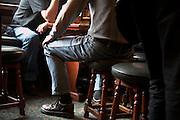Men sitting on stools inside a pub