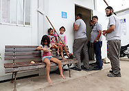 Jul 30, 2016; Rio de Janeiro, Brasil; Workers from the Olympic Park wait to buy lunch from one of the temporary container homes transformed by its residents into a make shift restaurant in Vila Autodromo. Mandatory Credit: Peter Casey-USA TODAY Sports
