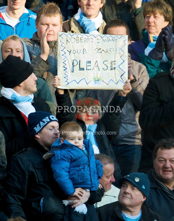 MANCHESTER, ENGLAND - Sunday, January 31, 2010: A young Manchester City supporter holds up a banner asking for manager Roberto Mancini's scarf during the Premiership match at the City of Manchester Stadium. (Photo by David Rawcliffe/Propaganda)