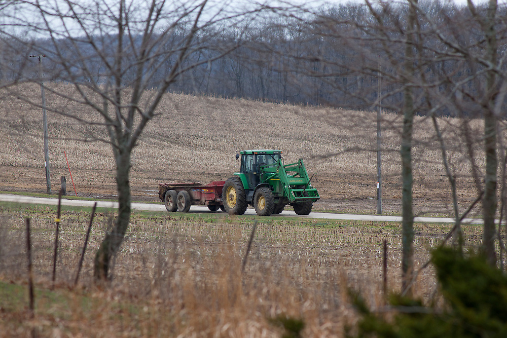 John Deere tractor and manure spreader on rural country road