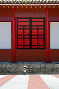 A young visitor walks past the striking exterior of Hokuden hall inside the grounds of Shuri Castlein Naha, Okinawa Prefecture, Japan, on June 24, 2012. The Hokuden was the central facility for political affairs, handling important judicial matters and state affairs. Photographer: Robert Gilhooly