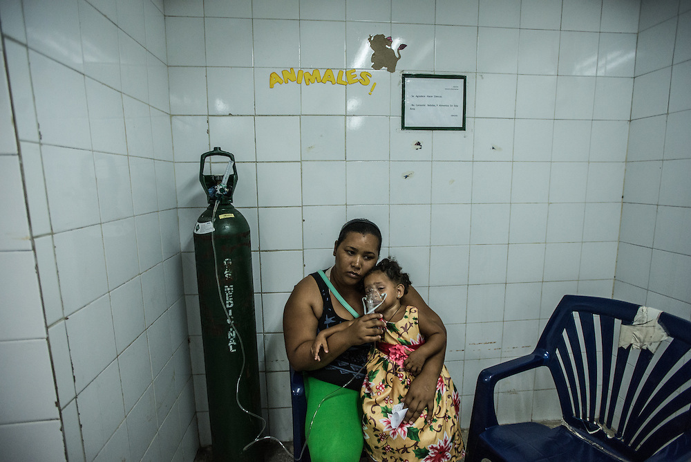 CATIA LA MAR, VENEZUELA - APRIL 12, 2016: Marbelis Reinoso gives her daughter, who suffers from asthma, a breathing treatment in the pediatric emergency room of a government-run clinic in Catia La Mar. Doctors here say they regularly have to turn patients away, because they don't have the majority of medicines  or medical equipment and supplies needed to give them medical attention.  When they do accept patients, they have to work with extremely limited resources. They said they regularly run out of medicines and supplies such as IV fluids, high-blood pressure medicine, baby asprin and masks. Despite having the largest oil reserves in the world, falling oil prices and wide-spread government corruption have pushed Venezuela into an economic crisis, with the highest inflation in the world and chronic shortages of food and medical supplies.   PHOTO: Meridith Kohut for The New York Times