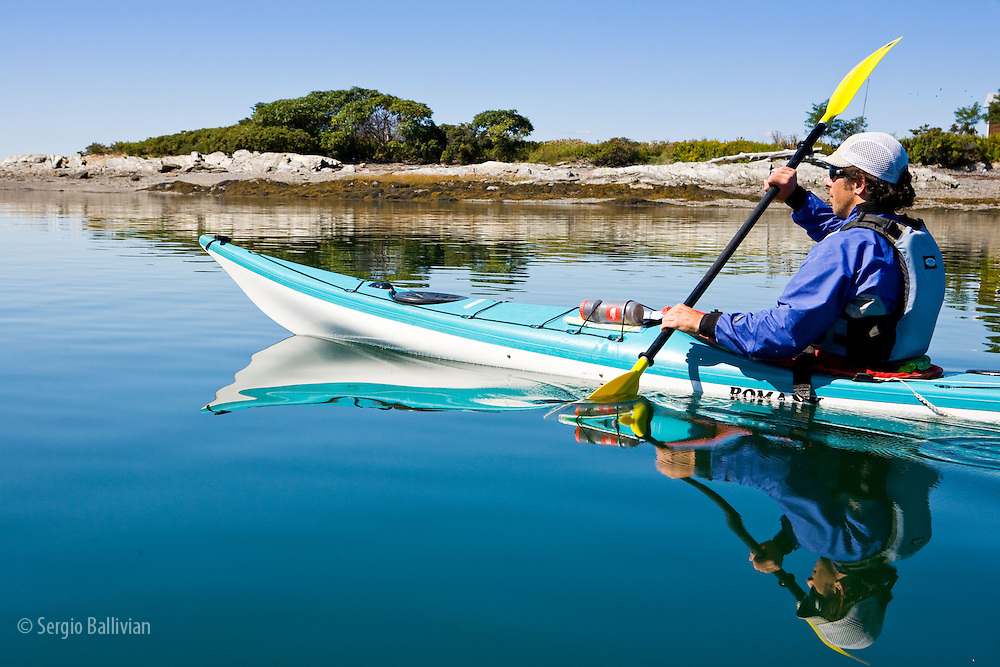 A man sea kayaks in a protected bay on Jewel Island off the coast of Maine in summer.