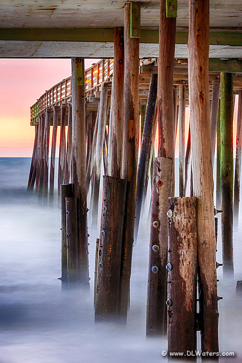 Long exposure turns the surf into mist under Kitty Hawk Pier at sunrise.