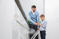 Father and son placing glass in dishwasher at kitchen
