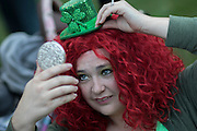 Aimee Norton puts the finishing touched on her outfit before the start of the St. Patrick's Day parade, Tuesday, March 17, 2015, in Savannah, Ga. Organizers have long billed the Savannah St. Patrick's Day parade as the nation's second largest based on the size of the procession, rather than the number of people watching. (AP Photo/Stephen B. Morton)
