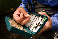 Details of hand-tied flies in a fly box of a fly fisherman as he prepares to fish in a steam near Estes Park, Colorado.