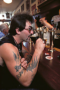 A tattooed patron sipping a beer at the bar of Triple Rock Microbrewery, formerly know as Roaring Rock. Berkeley, California. MODEL RELEASED.