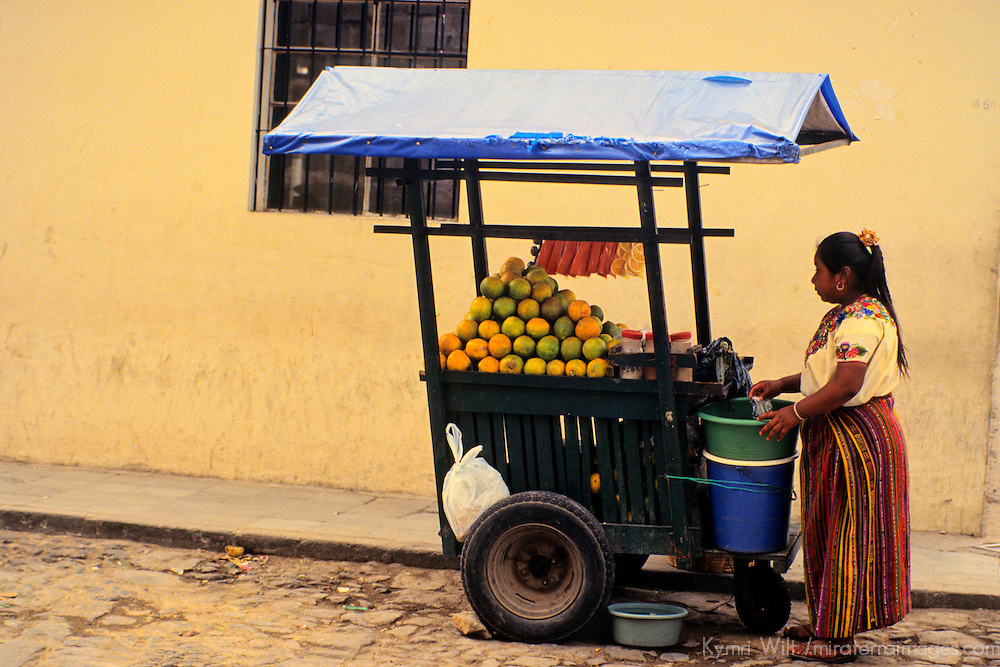 Central America, Guatemala, Antigua. A Guatemalan orange juice vendor attends her cart in Antigua, Guatemala.