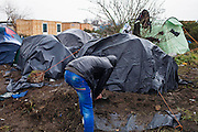 An Afghan man moves soil to weigh down the tarpaulin covering his tent. Many tents have proved inadequate in the wind and rain.