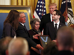 March 27, 2019 - Washington, District of Columbia, U.S. - United States President Donald J. Trump presents a posthumous Medal of Honor to the family of Staff Sergeant Travis Atkins during an East Room ceremony at the White House, in Washington, DC, Wednesday, March 27, 2019. Atkins' son, Trevor Oliver, received the award, along with his grandparents. Staff Sergeant Atkins earned the award for his selfless act in Iraq, 2007, where he shielded fellow soldiers from a suicide bomber, saving the lives of three  (Credit Image: © Martin H. Simon/CNP via ZUMA Wire)