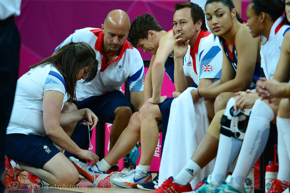 Jul 28, 2012; London, United Kingdom; Great Britain guard Stef Collins (third from left) reacts after an injury while being looked at by team medical staff members during the first half against Australia at Basketball Arena.