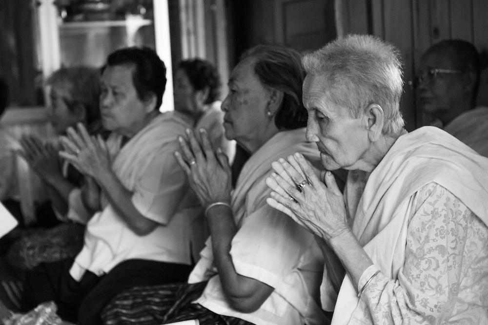 Buddhist women praying at home, on the first morning of Khmer New Year (Kompong Cham, Cambodia).