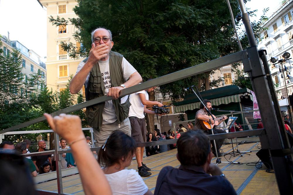 Commemorazione di Carlo Giuliani in Piazza Alimonda a Genova. Giuliano Giuliani, padre di Carlo, saluta i presenti da lato palco.