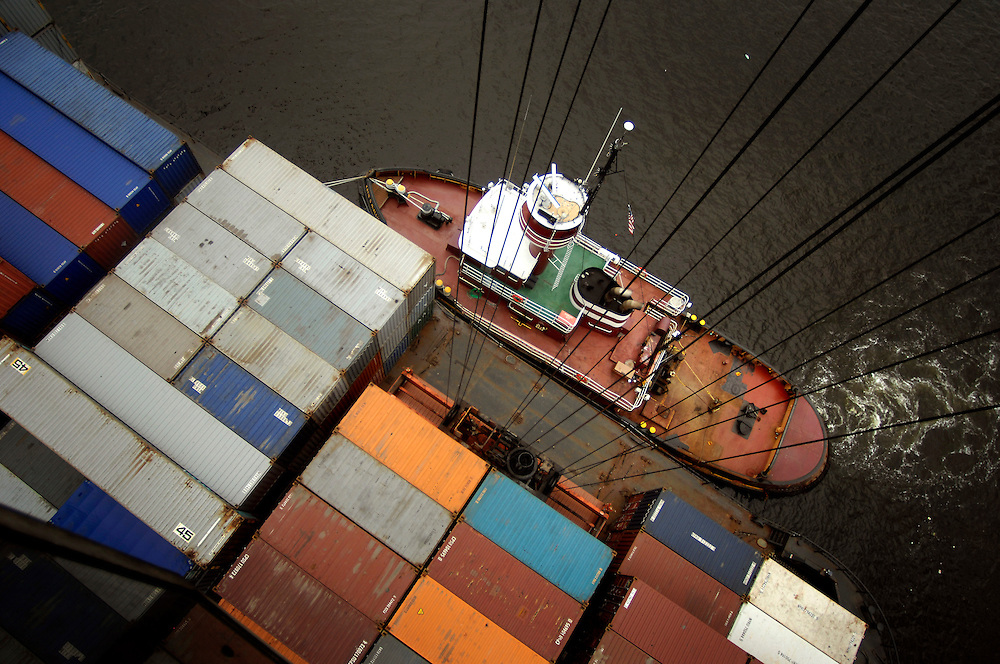 BALTIMORE, MD--8/5/08--A tug boat holds a barge stationary against the dock as a crane off-loads containers suspended from a system of cables at the Seagirt terminals in the Port of Baltimore in Baltimore, Md., Tuesday, Aug. 5, 2008. GLENN FAWCETT/SUN STAFF   MANDATORY CREDIT:  Baltimore Examiner and Washington Examiner OUT