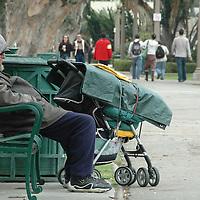A fomeless man sits on a Park bench at Palisades Park in Santa Monica.