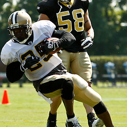 August 2, 2010; Metairie, LA, USA; New Orleans Saints running back Reggie Bush (25) runs away from linebacker Scott Shanle (58) during a training camp practice at the New Orleans Saints practice facility. Mandatory Credit: Derick E. Hingle