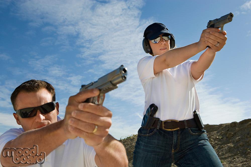 Man and woman aiming hand guns at firing range