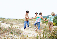 Children playing ring around the rosy on grassy beach