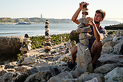 Johann Egger builds stone sculptures along the shore of the Tagus River in Lisbon, Portugal.