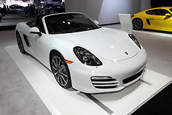 08  February 2013: 2013 Porsche Boxster high performance sports car. Chicago Auto Show, Chicago Automobile Trade Association (CATA), McCormick Place, Chicago Illinois<br /> <br /> 2013 PORSCHE BOXSTER: Porsche's new generation of mid-engine sports cars are on display at the Chicago Auto Show, with the release of the 2013 Porsche Boxster. Featuring a completely revamped chassis and lightweight design bodies, the Boxster and Boxster S are more fuel-efficient, faster and more agile. Both editions have considerably lower weight, longer wheelbase, wider track and larger wheels that significantly enhance the driving dynamics. Notice the stylish indentation in the door guiding your eye to the striking intake in the rear side section. Upfront are large lateral radiator openings and newly redeveloped halogen or Bi-Xenon headlights. Looking at the redesigned rear end, you'll see all LED techno taillights, and there is no longer any convertible-top compartment lid. Boxster continues with flat-six cylinder engines, in two performance sizes, starting with the entry-level 2.7 litre displacement that delivers 265 horsepower - ten hp more than its predecessor. Top-tier Boxster S is fitted with a 3.4L engine that produces 315 hp - five hp more than before. Consumers have a choice of the stock six-speed manual or optional seven-speed Porsche Doppelkupplungsgetriebe (PDK) (automatic) gearbox. The '13 Boxster retains it's unique oval tailpipe, white the Boxster S has a twin-flow double tailpipe. For serious drivers, there is the optional Sport Chrono package that allows for setting up the car for driving comfort in everyday use and for the weekend race circuits.