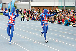 © Licensed to London News Pictures.  09/07/2012. STOKE MANDEVILLE, UK. Entertainers in union jack bodysuits entertain local school children waiting for the the Olympic Torch in Stoke Mandeville Stadium, birthplace of the Paraolympics on Day 52 of the Relay through Britain. Photo credit: Cliff Hide/LNP