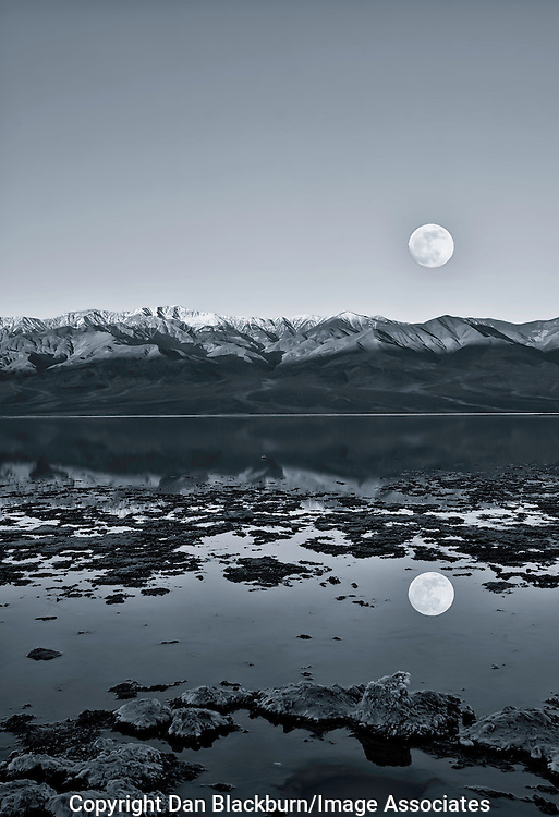 Full Moon sets over Telescope Peak and the Panamint Mountains and is Relected in Badwater,the lowest point in Death Valley California. Blue Tint.