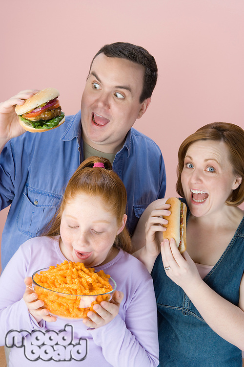 Overweight family holding unhealthy food