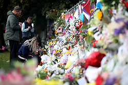 March 18, 2019 - Christchurch, New Zealand - People place flowers on a wall at the Botanical Gardens as a tribute to victims of the mosque attacks in Christchurch on March 17, 2019. At least 50 people were killed and 36 injured in mass shootings at two mosques in the New Zealand city of Christchurch Friday, 15 March. A 28-year-old Australian born man appeared in Christchurch District Court on Saturday charged with murder. (Credit Image: © Sanka Vidanagama/NurPhoto via ZUMA Press)