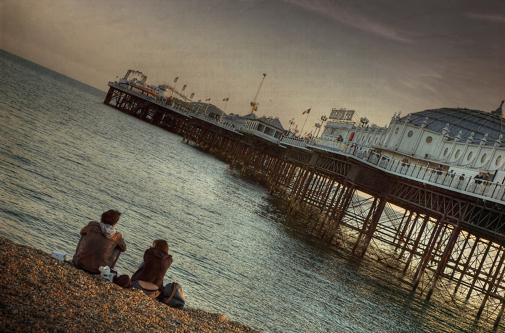 A young couple sitting on the beach beside Brighton pier in the evening