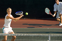 Tennis Player Swinging at Ball near tennis net; doubles partner squatting behind