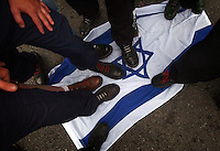 COEUR D ALENE, ID - JULY 17:  Members of the Aryan Nation step of an Israeli flag during the World Congress Parade held in Coeur d'Alene, Idaho, on Saturday, July 17, 2004. About 40 supporters and members marched in downtown Coeur d'Alene for the Aryan World Congress.  (Photo by Jerome Pollos/Getty Images)