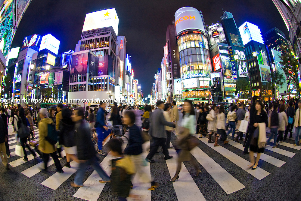 Busy street crossing at night in Ginza Tokyo