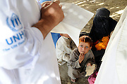 Afghan returnees cross the border from Pakistan to Torkham on September 7, 2008, Torkham, Afghanistan.  The returnees recieve vaccinations, money, and general assistance from UNHCR.  They are also warned about the dangers of landmines and unexploded ordinance.