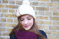 Happy young woman wearing knit hat and scarf looking down