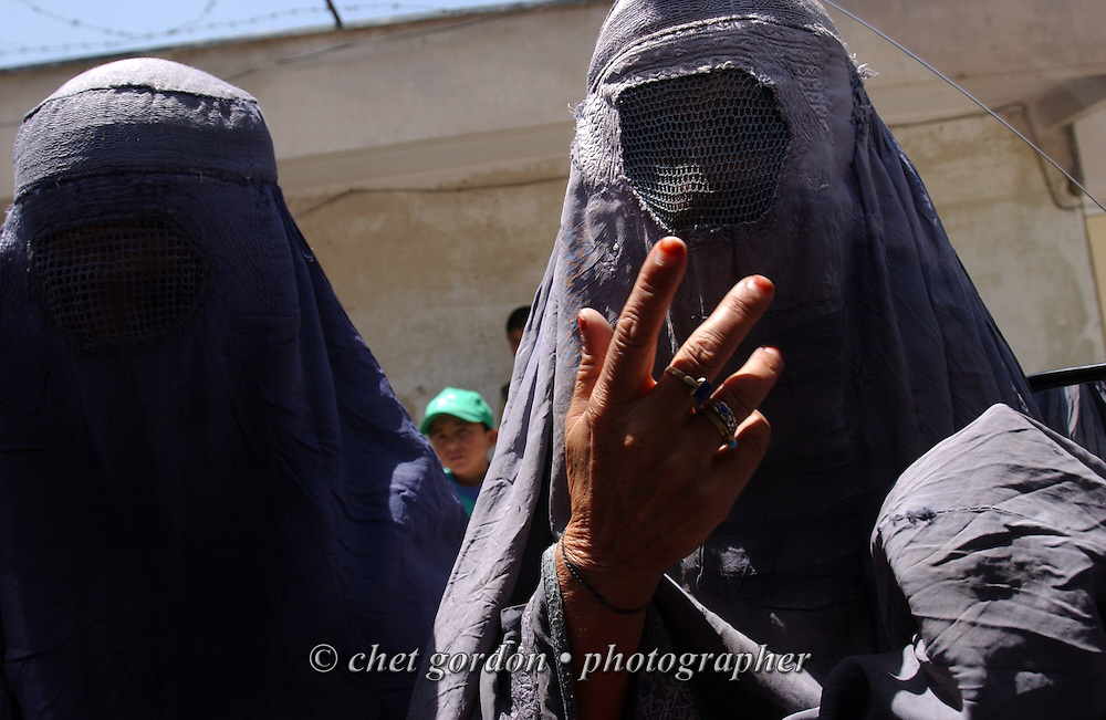 Afghan women dressed in traditional burkas approach a vehicle asking for money in Kabul, Afghanistan on Sunday, May 26, 2002.