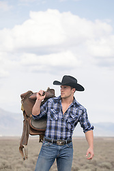 sexy cowboy holding a saddle outdoors
