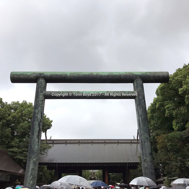 August 15, 2017, Tokyo, Japan: Passing through Yasukuni Shrine's historic gate with the Imperial Chrysanthemum Seal of Japan, tens of thousands came to pay their respects to Japan's war dead on the 72nd anniversary of the end of World War II. Yasukuni Shrine is the national Shinto shrine where nearly 2.5 million war dead from the past 150 years are enshrined. Visits to Yasukuni by top Japanese politicians continue to outrage China and South Korea because it honors 14 World War II class A war criminals who are also enshrined there. Even so, dozens of Japanese lawmakers visited Yasukuni Shrine today, while PM Shinzo Abe sent a ritual offering via his emissary. Photo by Torin Boyd.